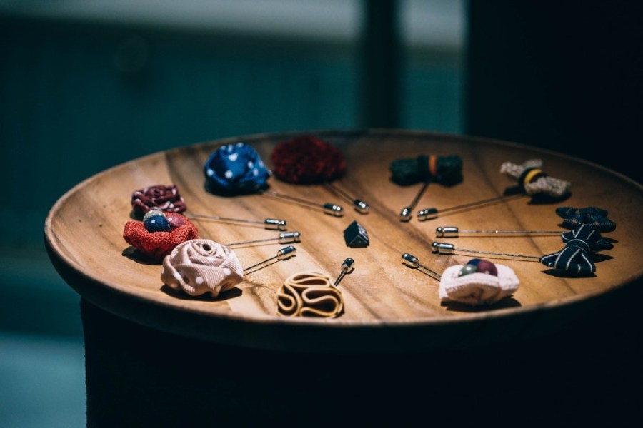 Suit-Pins-Displayed-for-Sale-on-a-Wooden-Board