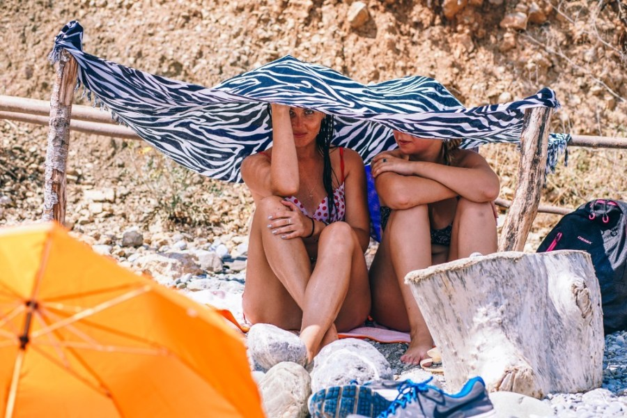 Two-Girls-under-an-Improvised-Umbrella-at-the-Beach