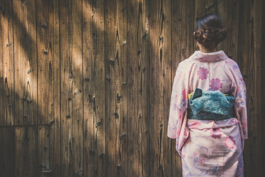 Woman-dressed-in-a-Japanese-Kimono-Standing-in-front-of-a-Wooden-Wall