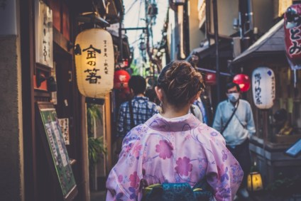 Woman-in-Traditional-Japanese-Clothes-Walking-Through-an-Alley-in-Kyoto