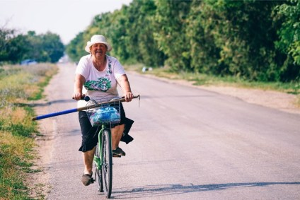 Old-Woman-Smiling-at-the-Camera-while-Riding-a-Bicycle