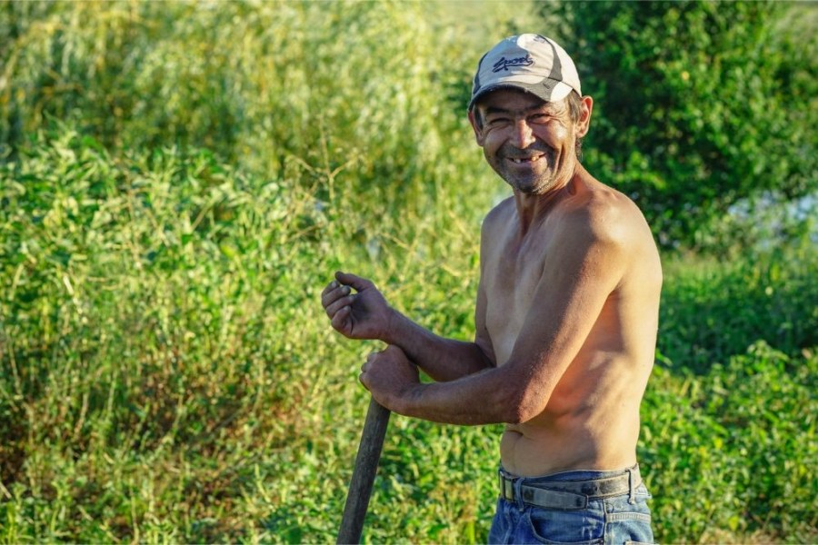 Shirtless-Man-Smiling-at-the-Camera-While-Working-in-a-Field