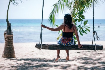 Woman-Enjoying-the-Nice-Weather-on-a-Beach-Swing