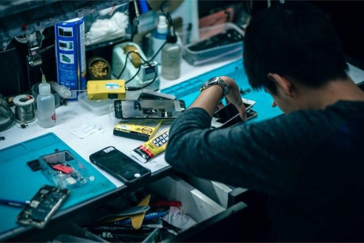 Man-Fixing-iPhones-in-a-Mobile-Repair-Shop