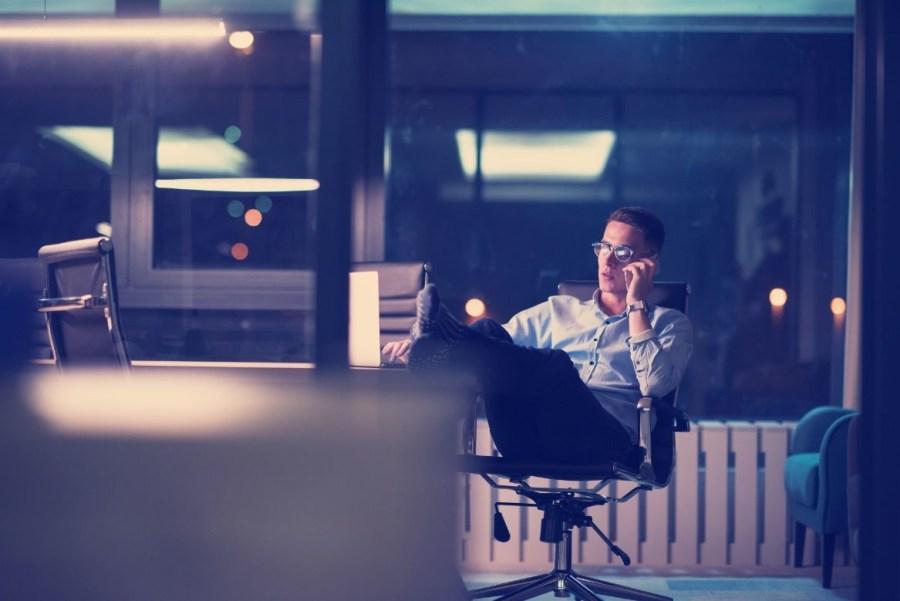 businessman-using-mobile-phone-in-dark-office-P598HZ3