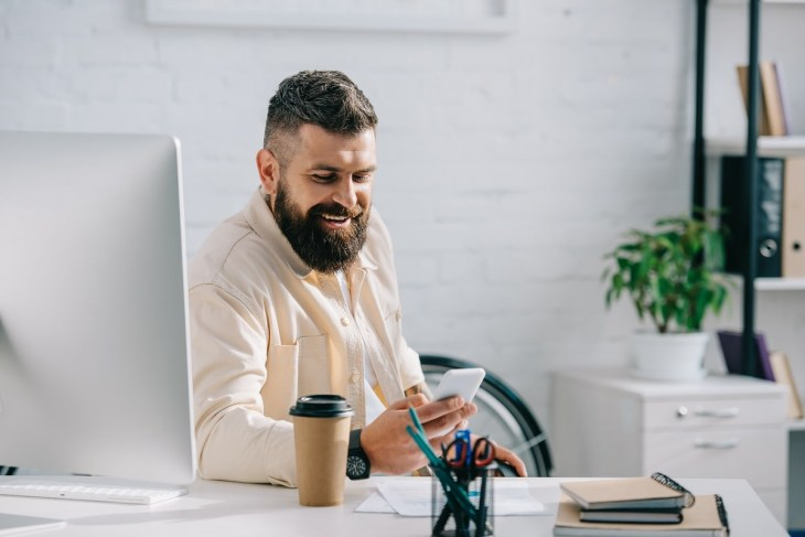 laughing businessman sitting in office and looking at smartphone
