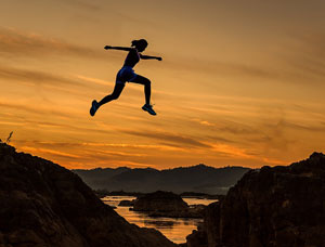 Person jumping over a gully at sunset