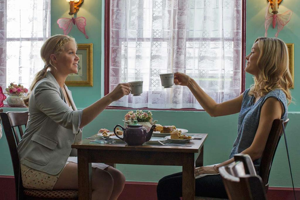 Brie Larson and Amy Schumer cheers with cups in Trainwreck