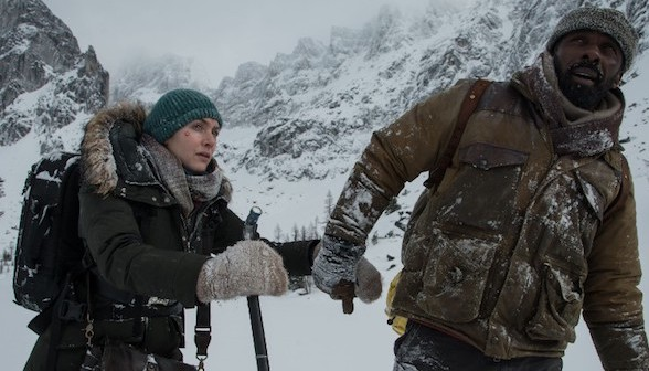 Kate Winslet and Idris Elba holding hands in the snow in The Mountain Between Us