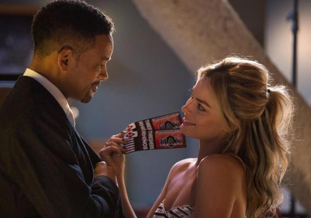 Margot Robbie with football tickets for Will Smith in Focus