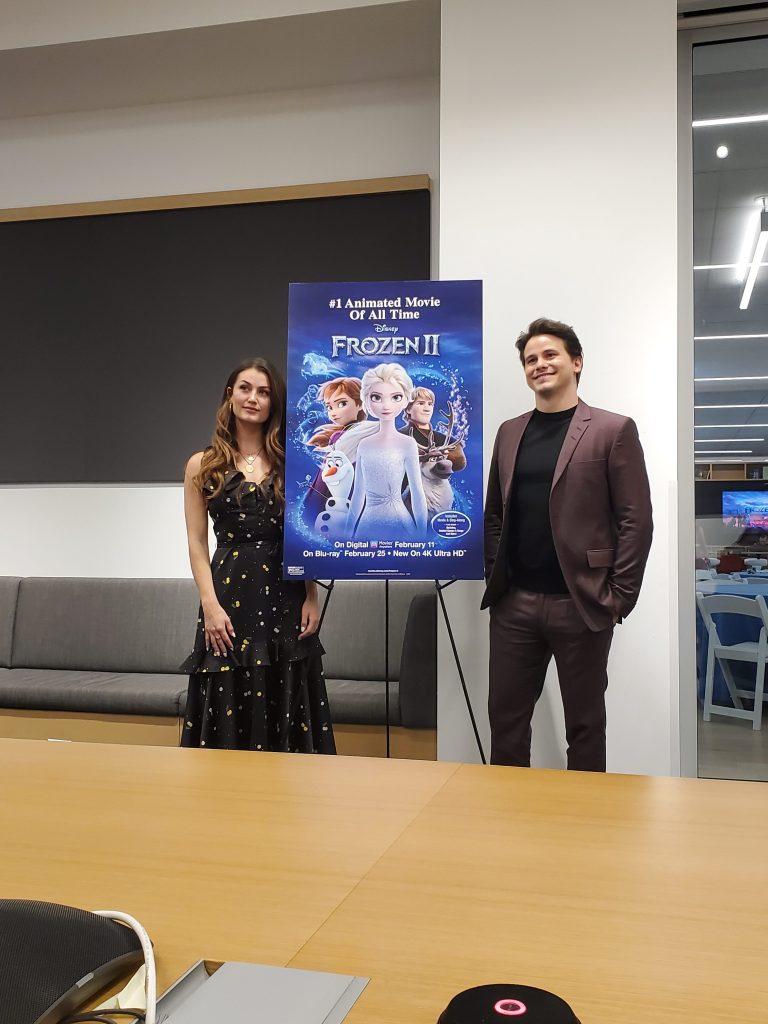 Actors Rachel Matthews and Jason Ritter in front of a Frozen II poster