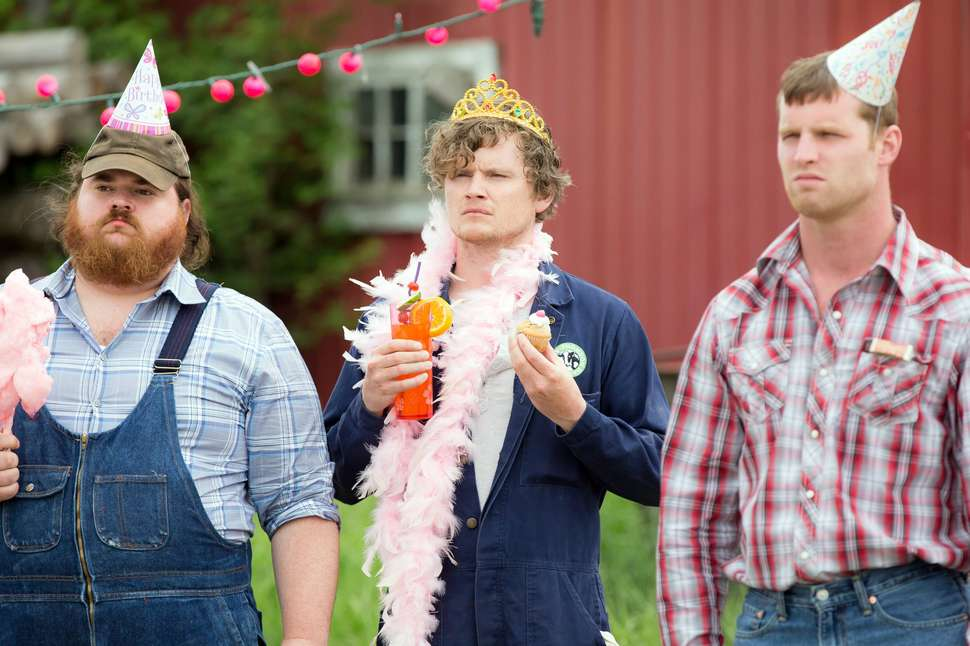 Three men standing outside. One wearing overalls with cotton candy and a birthday hat, one in a blue jumpsuit with a feather boa and tiara, and the third in flannel with a birthday hat. Letterkenny