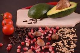 avocado en kruidnagel op plankje met eromheen 3 tomaatjes rijst hazelnoten, kruidnagel en mais