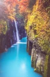 Lichtblauw water tussen twee rotswanden en gekleurde bomen