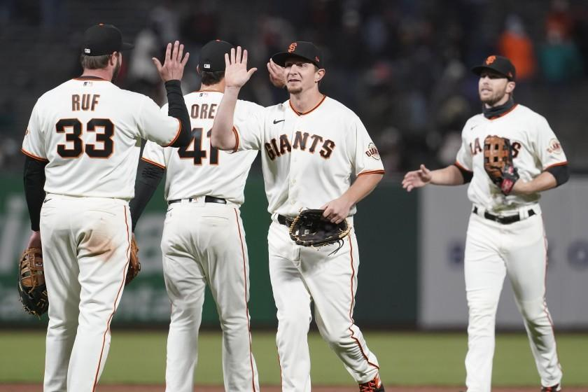 San Francisco Giants players celebrate after defeating the Miami Marlins in a baseball game in San Francisco, Thursday, April 22, 2021. (AP Photo/Jeff Chiu)