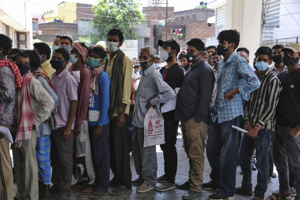 People wearing face masks as a precaution against the coronavirus line up without any physical distancing to get tested for COVID-19 at a government hospital in Jammu, India, Monday, April 19, 2021. India now has reported more than 15 million coronavirus infections, a total second only to the United States. (AP Photo/Channi Anand)