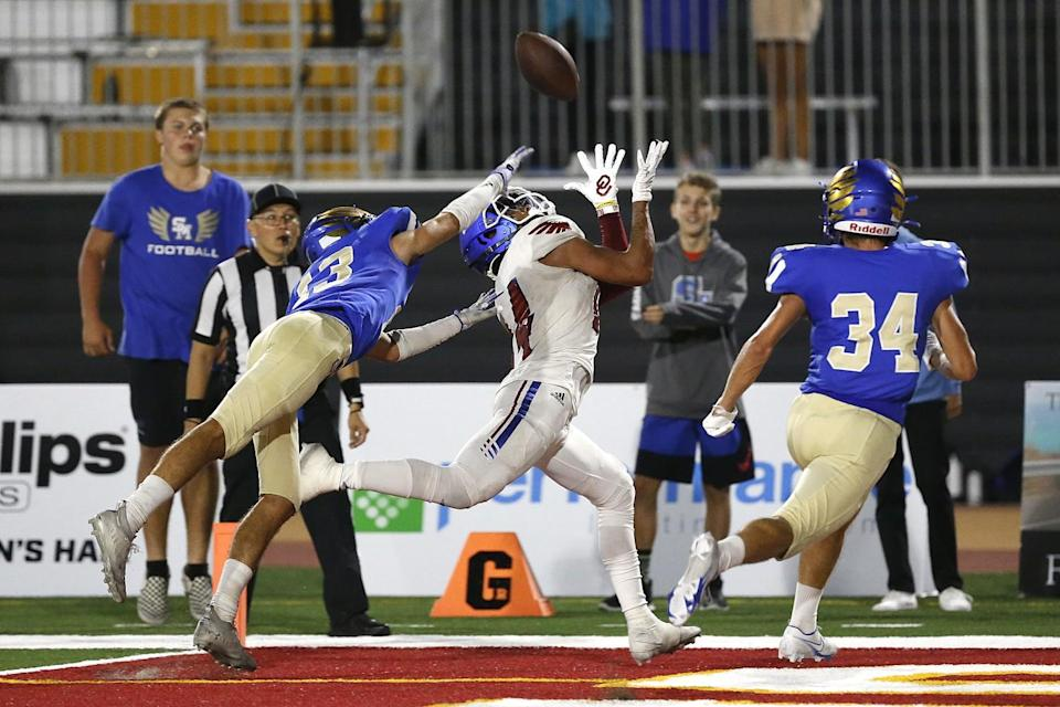 Los Alamitos's Makai Lemon attempts to haul in a pass while under pressure from Santa Margarita's Donovan Comestro.
