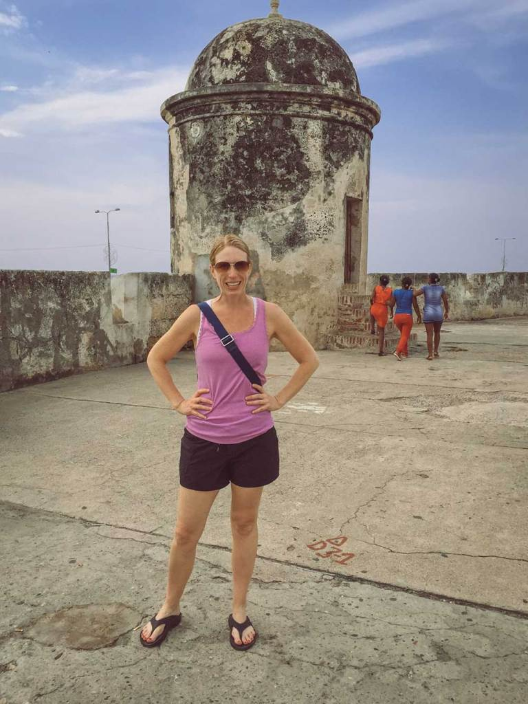 Kelly on a wall with tower in background, Cartagena, Colombia, Fantasy Aisle Travel