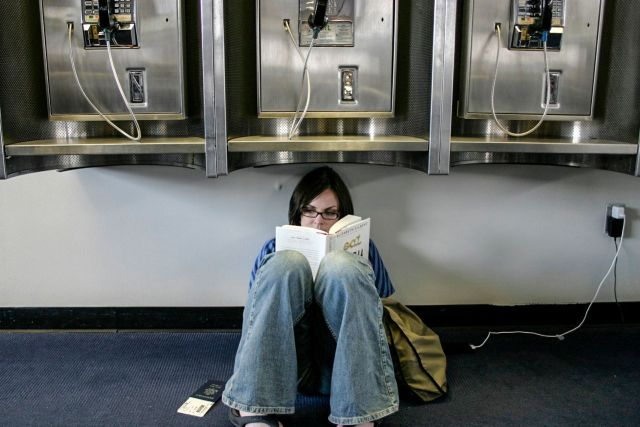 Woman charging her phone while sitting under payphones