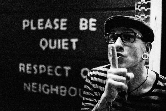 Please be quiet written on a wall with a male making a shh motion with hands