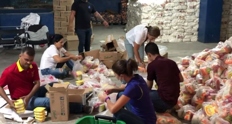 Personas preparando las bolsas de alimentos que Nacho regaló en Margarita