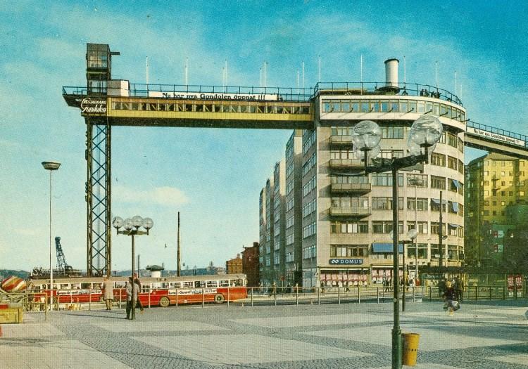 Vykort med Katarinahissen, restaurang Gondolen, KF-huset och SL-s röda bussar vid Slussen i Stockholm