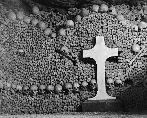 Huesos humanos con una cruz al frente en las catacumbas de París