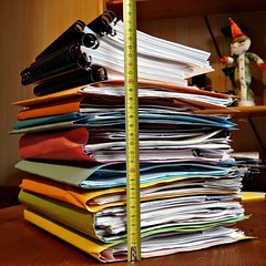 Stacks of documents being measured with a tape measure