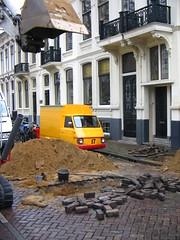 Vespacar near a hole in the street