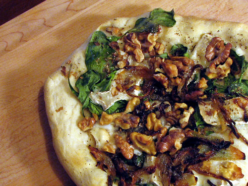 Pizza with arugula, goat brie, walnuts, caramelized onions, and walnut oil