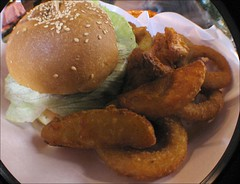 hamburger with potato wedges and onion rings