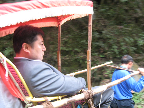 Businessman riding on the shoulders of porters through the park in China