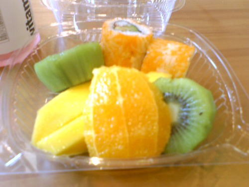 a lunch of fruit and sushi in a takeout container