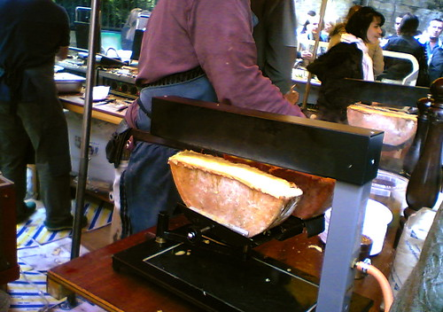 Raclette cheese being scraped onto a plate.