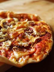 Prosciutto, anchovy and onion pizza.