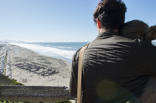 Two people watched as thousands gathered on Ocean Beach, forming the word RESIST!, February 11, 2017