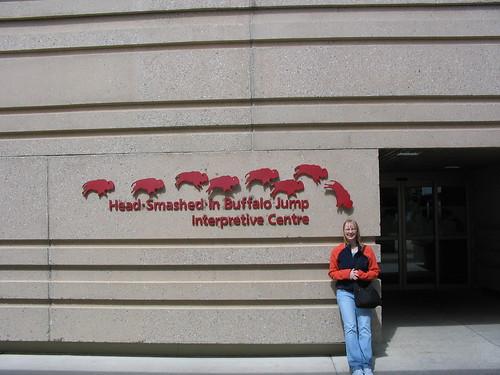 A lady standing below an image of a falling buffalo.