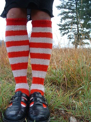 a shot of two legs from the knees down, adorned with red and white stripy wool socks