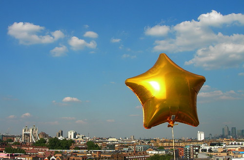 Photo of a balloon in the shape of a gold star with London in the background