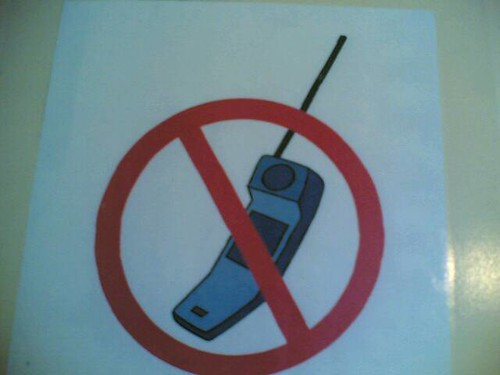 """Librarian completely disregarding his own """"no mobiles"""" sign by hugovk."""