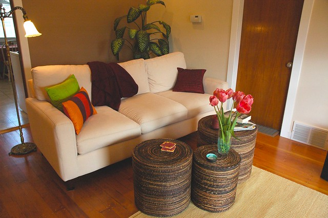 Peggy's Zen living room makeover, white sofa, pink tulips, bright pillows, maroon throw, natural woven drum shaped tables, jute rug, refinished floor, old brass floor lamp, Seattle, Washington, USA