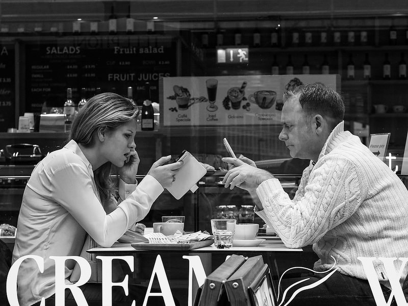 Imagen gratis de una pareja con los móviles en una cafetería