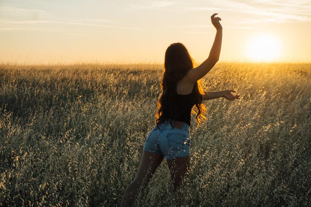 Imagen gratis de una chica intentando atrapar el sol