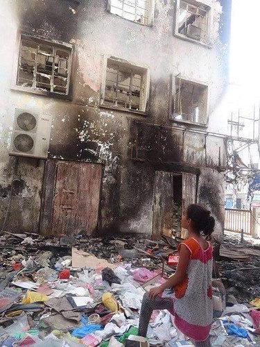 Niña en Yemen frente a un edificio incendiado por los bombardeos
