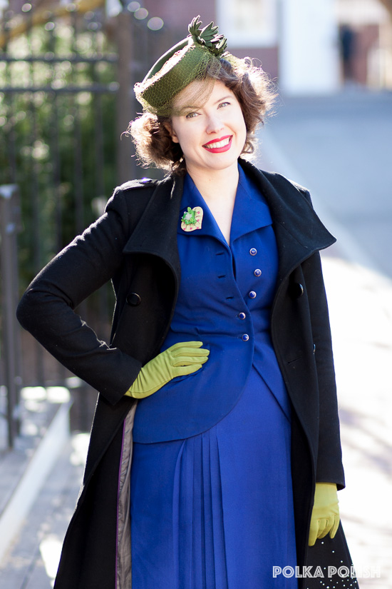 1940s blue suit jacket paired with a green tilt hat and gloves, a novelty brooch, and a black coat