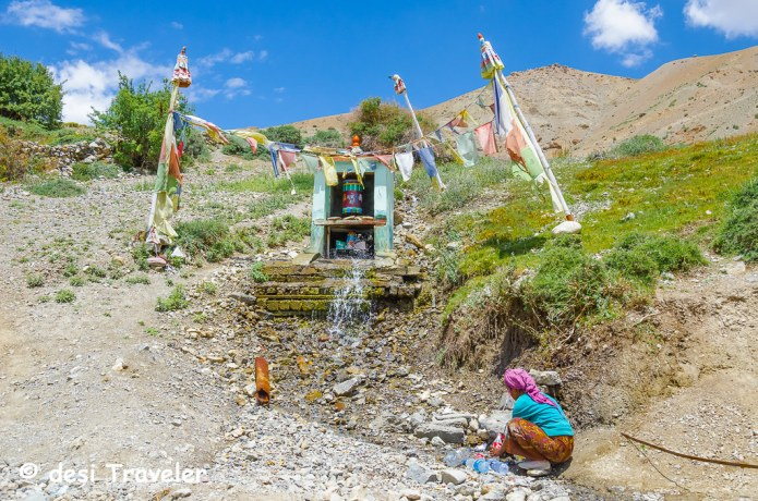 A women filling water from a mountain spring Spiti
