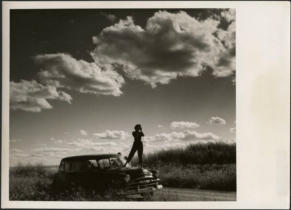 Audrey James standing on the hood of Helen Salkeld's station wagon taking a photograph of the prairies... / Audrey James debout sur le capot de la voiture familiale de Helen Salkeld prennant une photo des Prairies...