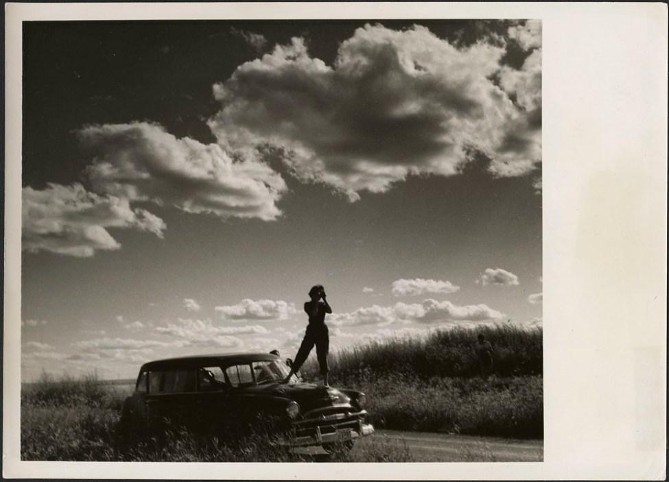 Audrey James standing on the hood of Helen Salkeld's station wagon taking a photograph of the prairies... / Audrey James debout sur le capot de la voiture familiale de Helen Salkeld prennant une photo des Prairies...