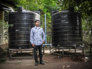 Ananta stands infront of the two 5000 litres capacity rainwater harvesting tanks at Melamati Government Junior Basic School.