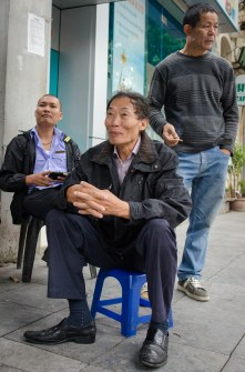 Three Men Siting in Front of Store